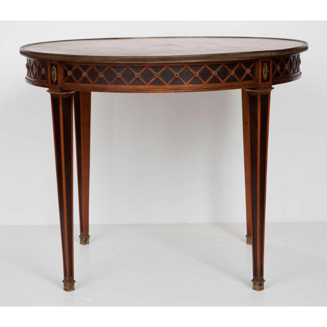 A Louis XVI style gueridon of exceptional quality and workmanship. Attributed to Maison Jansen, this table has ebonized,...