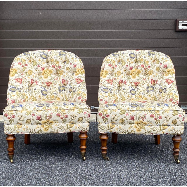 A quality pair of slipper chairs with floral tufted back upholstery and brass casters on front legs.