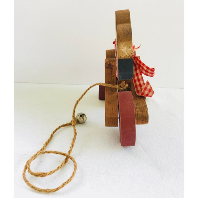 Vintage decorative wood teddy bear on rolling wheels with cord and bell finial. This cute vintage decorative toy is a...