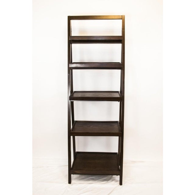 Beautiful dark wood bookcase with five shelves increasing in width from smaller to larger.