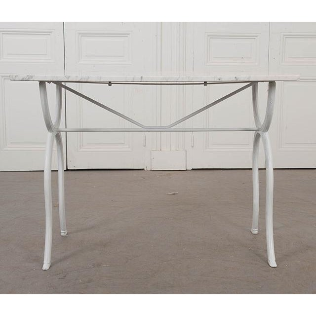 A French late 19th century white-painted and marble-top bistro table, c. 1890. The white marble top with grey veining...