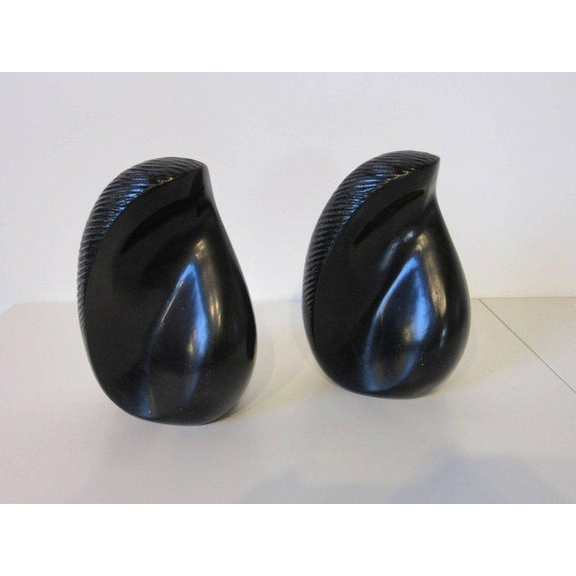 A pair of sculptural metal bookends in satin black and copper applied finish with design embellishments to the side and...