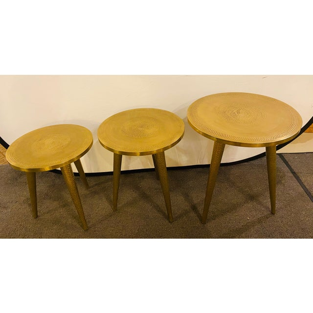 Set of three hand-hammered brass Mid-Century Modern style nesting side tables. Each table features beautifully handcrafted...