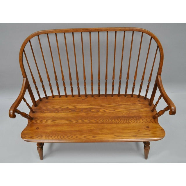 Solid Oak Wood Windsor Colonial Style Bench. Signed H.C. Co. to the base. Item features beautiful wood grain, quality...