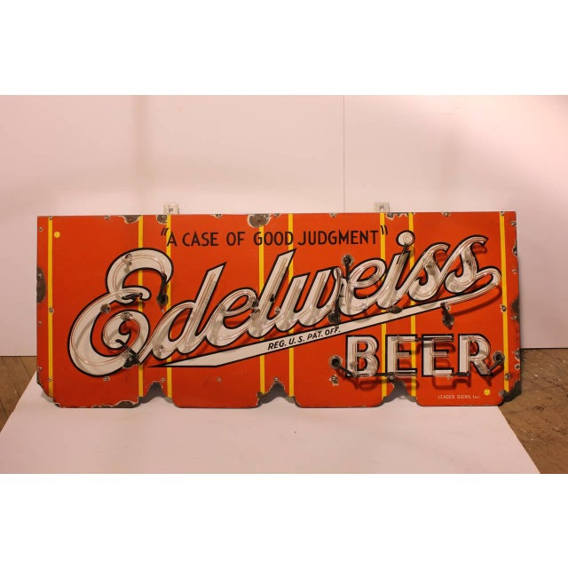 "1930s porcelain advertising sign for ""Edelweiss Beer a Case of Good Judgment"" sign with a red neon."