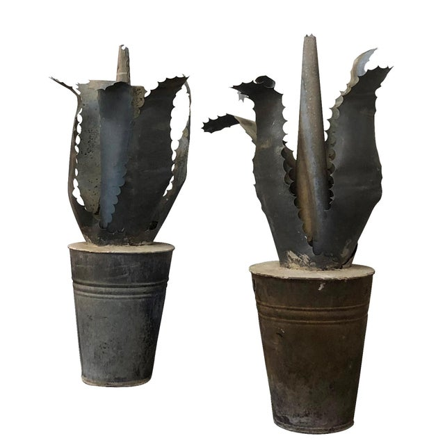 A pair of uniquely decorated Mid-Century Modern zinc finials in the shape of succulents Agavi, stylized planters are...