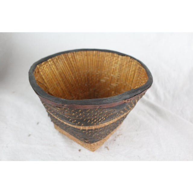 Handwoven grass and leather tribal basket with solid base in brown and tan.