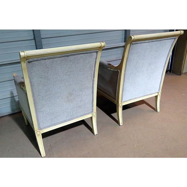 Pair of Directoire style distressed finished bergeres with blue upholstery.