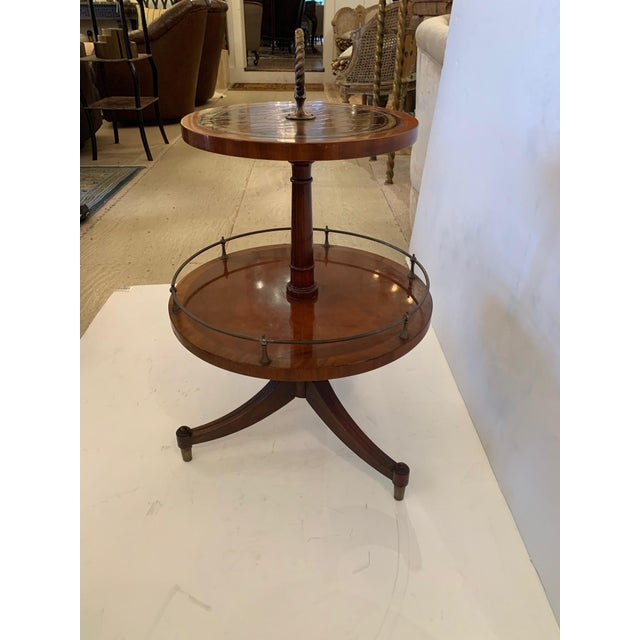 Unusual very functional two tier round mahogany side or drinks table having handsome tooled leather surfaces, twisted...