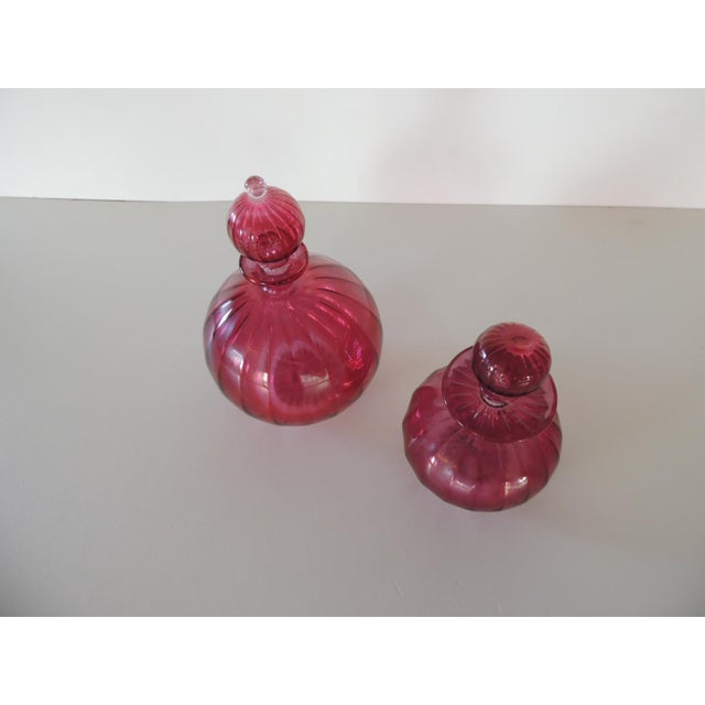 """Pair of Egyptian hand blown cranberry perfume bottles with stoppers. Sizes: Large: 4"""" D x 5.5"""" H Small: 3"""" D x 4"""" H."""