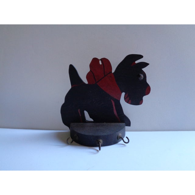 A sweet vintage key rack holder in the shape of a Scottish Terrier Dog. Circa 1930s wooden rack is painted black, with...