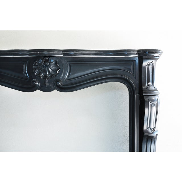 Antique marble fireplace from Belgium from the 19th century in style of Louis XV. The black marble is called 'Noir de...