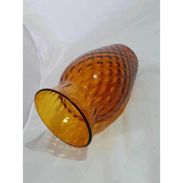 A gorgeous antique hand nblown glass vase in amber colored glass with a pontel base that testifies to it's age. Probably...