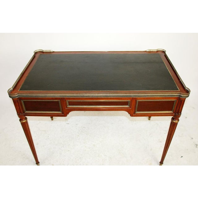 Directoire Style bureau plat/desk in mahogany with brass galllery and black leather writing surface. Mid 20th Century.