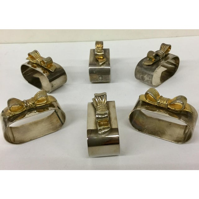 A very cool set of oval shaped napkin holders with gold tone bows on top. The gold bows have faded over time as these are...
