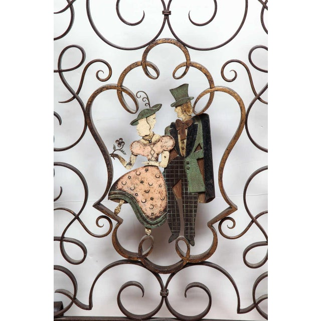 Art Deco figural fire screen in patinated and wrought iron with a motif of volutes and polychrome couple in the central...