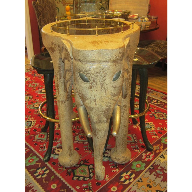An Elephant bar table and stools by Marge Carson from the late 20th and early 21st century. The bar with brass-gallery and...