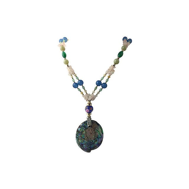 Statement necklace featuring a large centrally set abalone shell on a multi-strand chain of art glass, glass, and quartz...