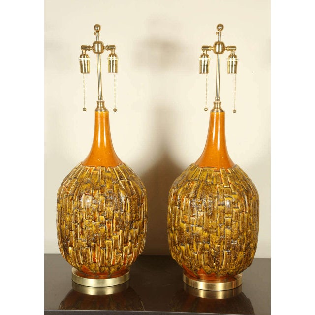 Pair of large stylish Mid-Century ceramic table lamps. They have been newly rewired and outfitted with brass bases and...