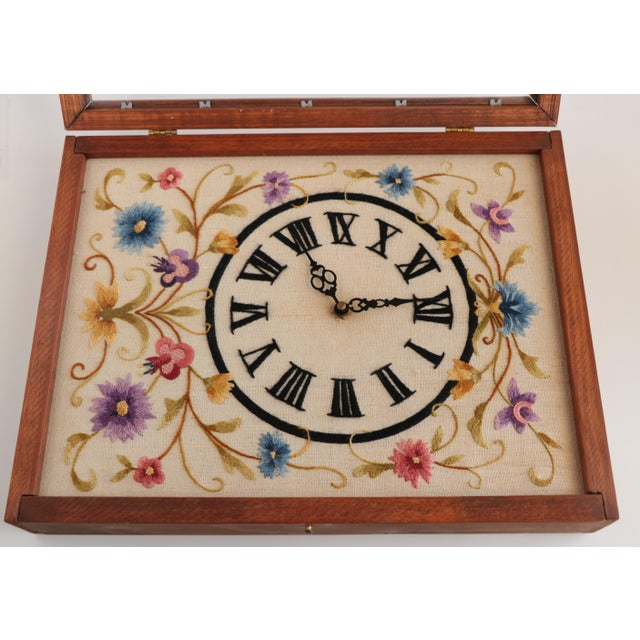 Large framed crewel embroidery clock with stitched Roman numeral face and Jacobean floral vines. The wooden case has a...