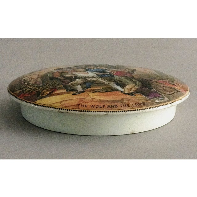 """Victorian Staffordshire Prattware multicolored transfer printed pot lid with the title """"The Wolf and the Lamb."""" It depicts..."""