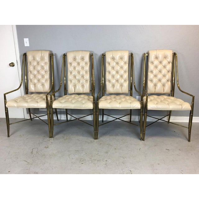 Rare set of four faux bamboo frame dining chairs by Mastercraft in brass. Original ivory vinyl upholstery. No tears or...