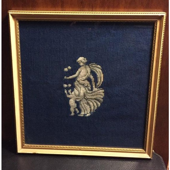 This a vintage framed needlepoint picture of a Greek goddess and cupid in white on a navy background. The gold frame has a...