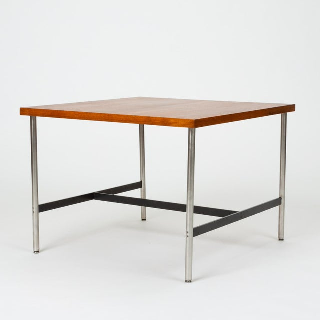 A modernist children's table by Herman Miller with a square tabletop and metal frame. Four round legs of brushed steel...