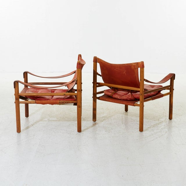 A stunning pair of authentic vintage Arne Norell safari sirocco chair in rosewood and rare red leather. Made by Norell...