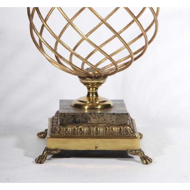20th century brass orb in the Hollywood Regency style with cone finial on square marble base and four paw feet. Made in...