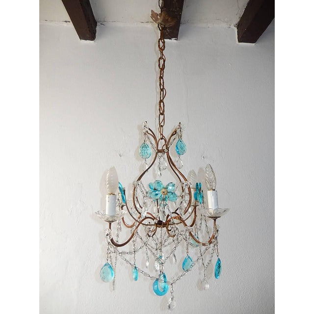 Housing four lights, sitting in crystal bobeches. Re-wired and ready to hang. Adorning aqua flowers made of prisms, clear...