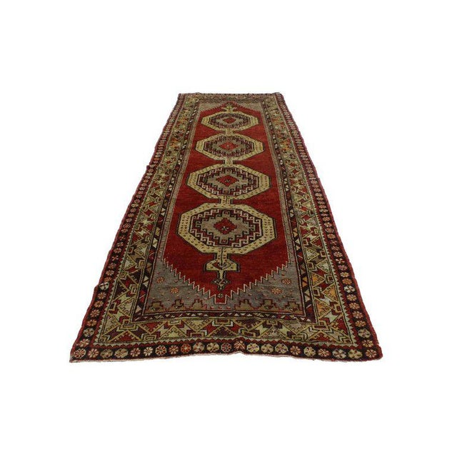 This hand-knotted wool tribal style Oushak runner features four intricate rod amulets each filled with a garnet diamond...