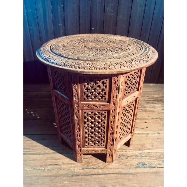 A beautiful Indian Moroccan carved side table made of rosewood, and easily fold-able. Heavy carving adorns every inch of...