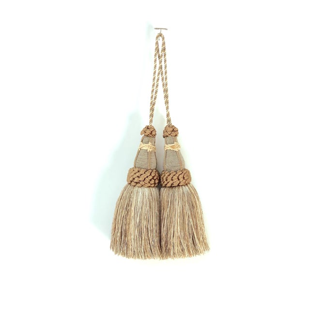 Pair of handmade khaki and bronze colored key tassels with looped ruche, twisted cord and full skirt. Skirting contains a...