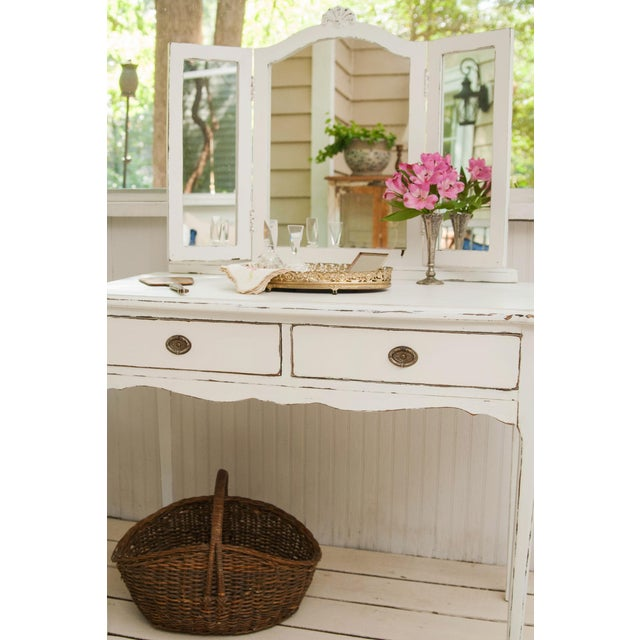 Vintage French distressed vanity, hand-painted white. The piece features a 3-sided mirror, 2 drawers, and Queen Anne style...