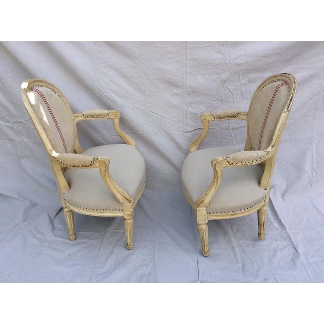 A pair of French side chairs in linen. The backs are in a rough tan linen with a red stripe and the seats are a fine tan...