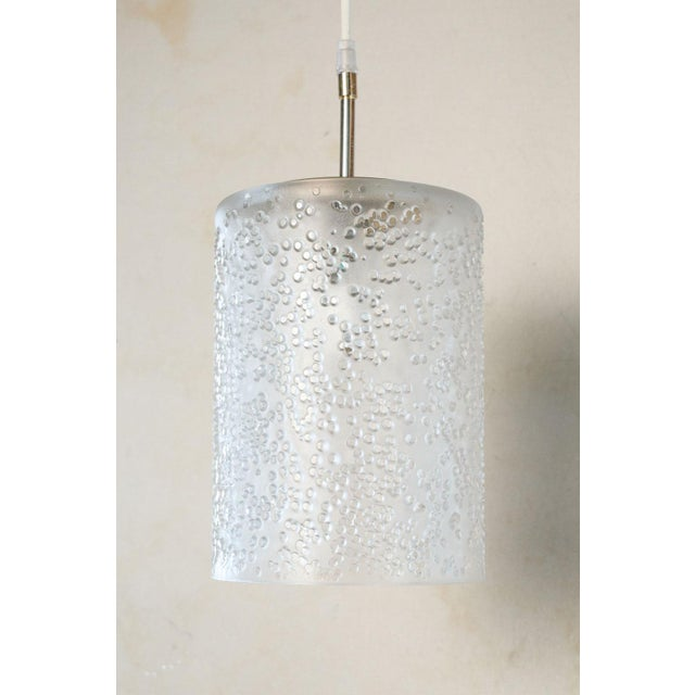 Pair of mid-century Swedish pendants in semi-transparent frosted glass. These modern cylinder shaped lights each...