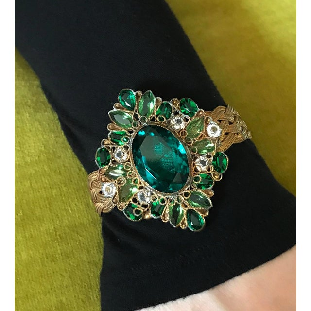 Circa 1940s braided chain bracelet by Hobé with a stunning emerald green faceted glass jeweled centerpiece and has a...