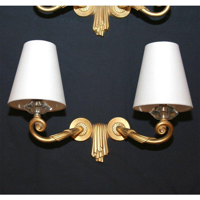 "A pair of French Art Deco ""Draperie"" wall sconces by Jules Leleu, two-armed, in gilt bronze, crystal and fabric shades."