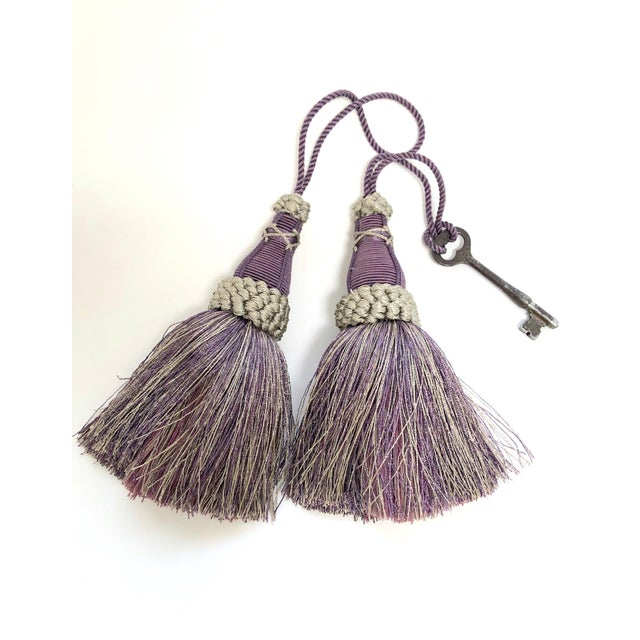 Pair of handmade amethyst and grey colored key tassels with looped ruche, twisted cord and full skirt. Skirt has a blend...