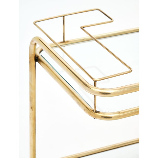 Mid-century brass and glass bar cart with beautiful modern curves and bottle holders. The brass structure features...