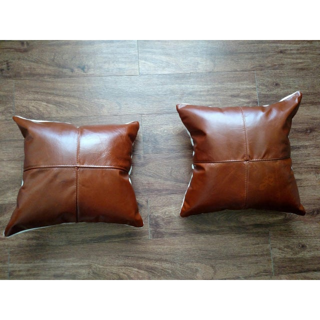 Set of 2 saddle brown pillows. Leather on front with cotton fabric on back. Zipper Closure. Made in USA. 100% Polyfiber...