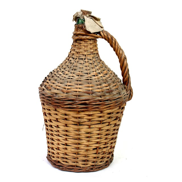 Vintage or antique thick green glass wine jug with original cloth and cork stopper, covered in hand-woven wicker with...