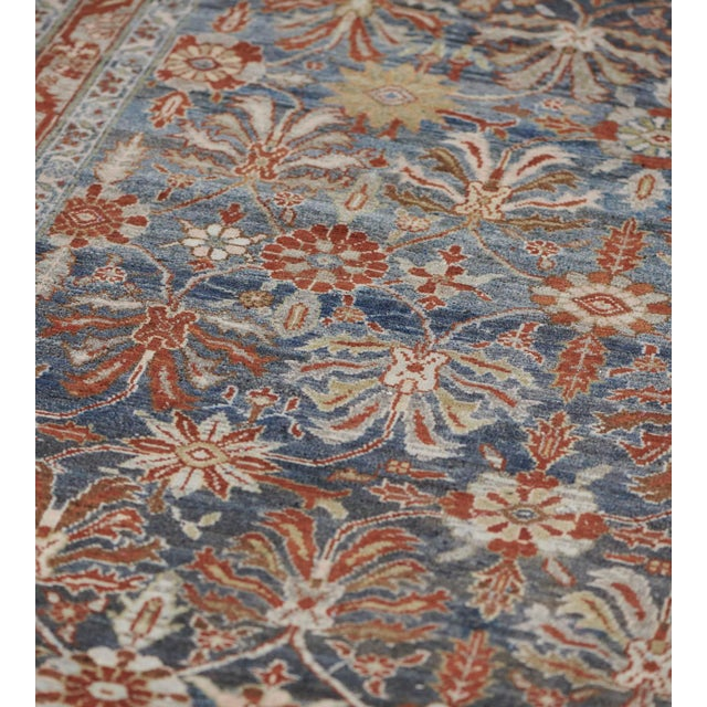 This antique Malayer rug has a shaded blue field with an overall design of ivory, fox-brown and sandy-yellow palmettes and...