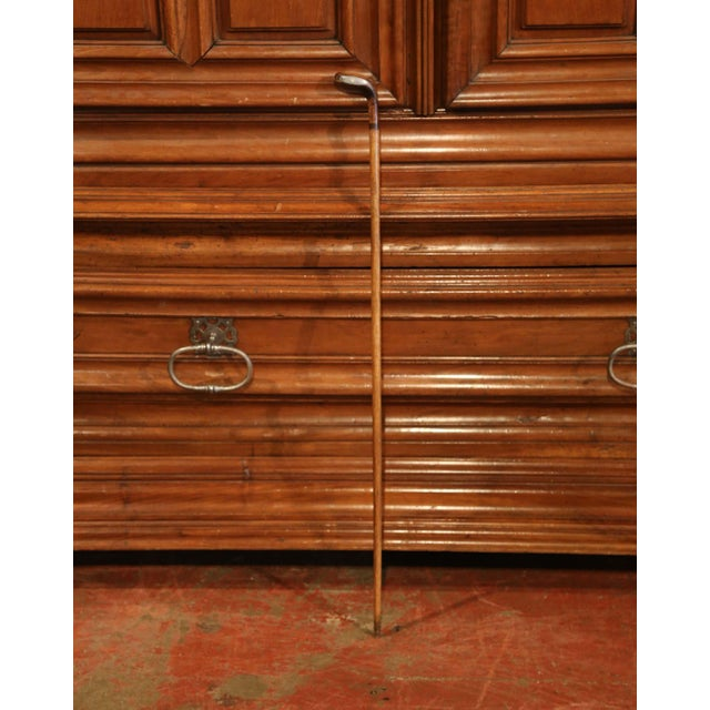 This unusual antique fruitwood cane was created in England, circa 1910. The walking stick features a plain stem and a...