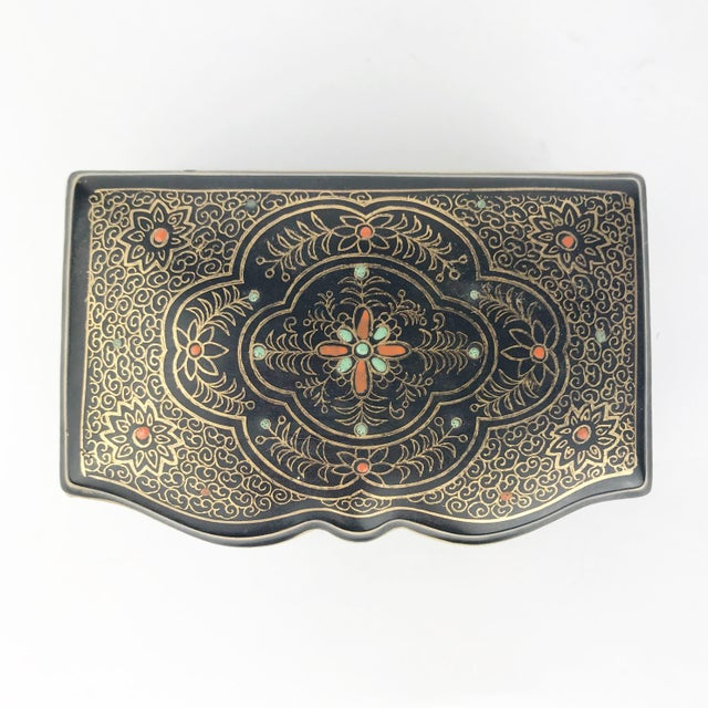 A beautiful hand painted rectangular ceramic lidded jewelry box! This black footed box has delicate gold scrollwork and...