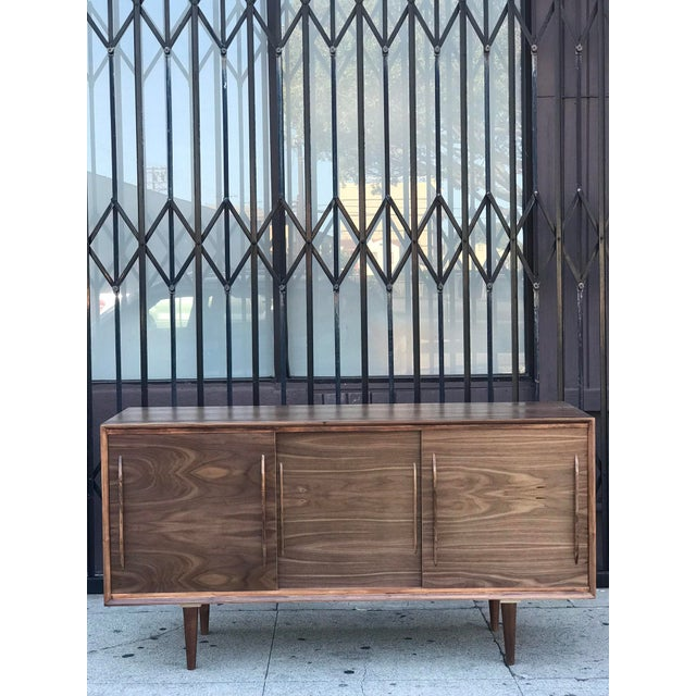 Contemporary Media Stand With Arched Handles now available in walnut. Modern touch provided with its geometric design...