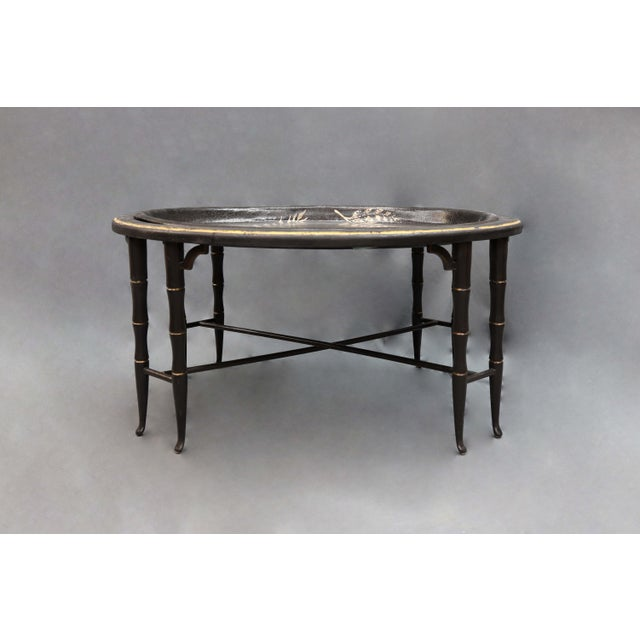 Table painted with silver colored leaves and 4 pairs of faux bamboo legs in black/gold with an opening at the top for the...