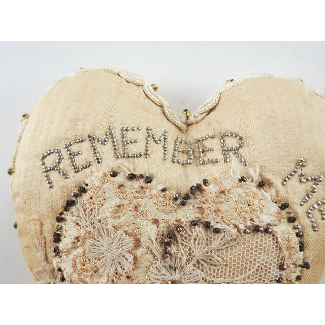Circa 1900 cream silk pincushion. Made as a gift with Remember Me spelled out with silver steel pins. Soutache braid...