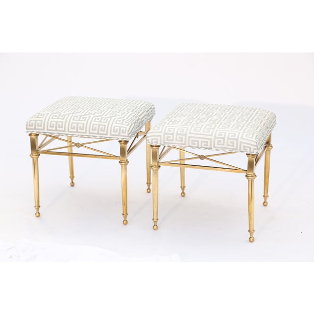 Pair of stools, each having a square upholstered crown seat, on frame of brass, raised on round, tapering legs, joined by...